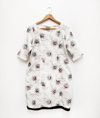 shift dress with princess seams and a black contrasting band along the hemline. dress is white with a black and red rose print