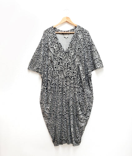grey and black snake print dress in a vneck kaftan style, on a hanger