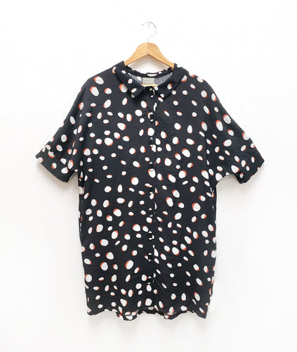buttoned shirt dress in a cocoon shape. fabric is black with white and terracotta colored dots