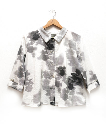 white button up blouse with a cloudy print in different tones of grey. blouse has a buttons and a small split on either cuff. twin horizontal buttons go down the blouse front