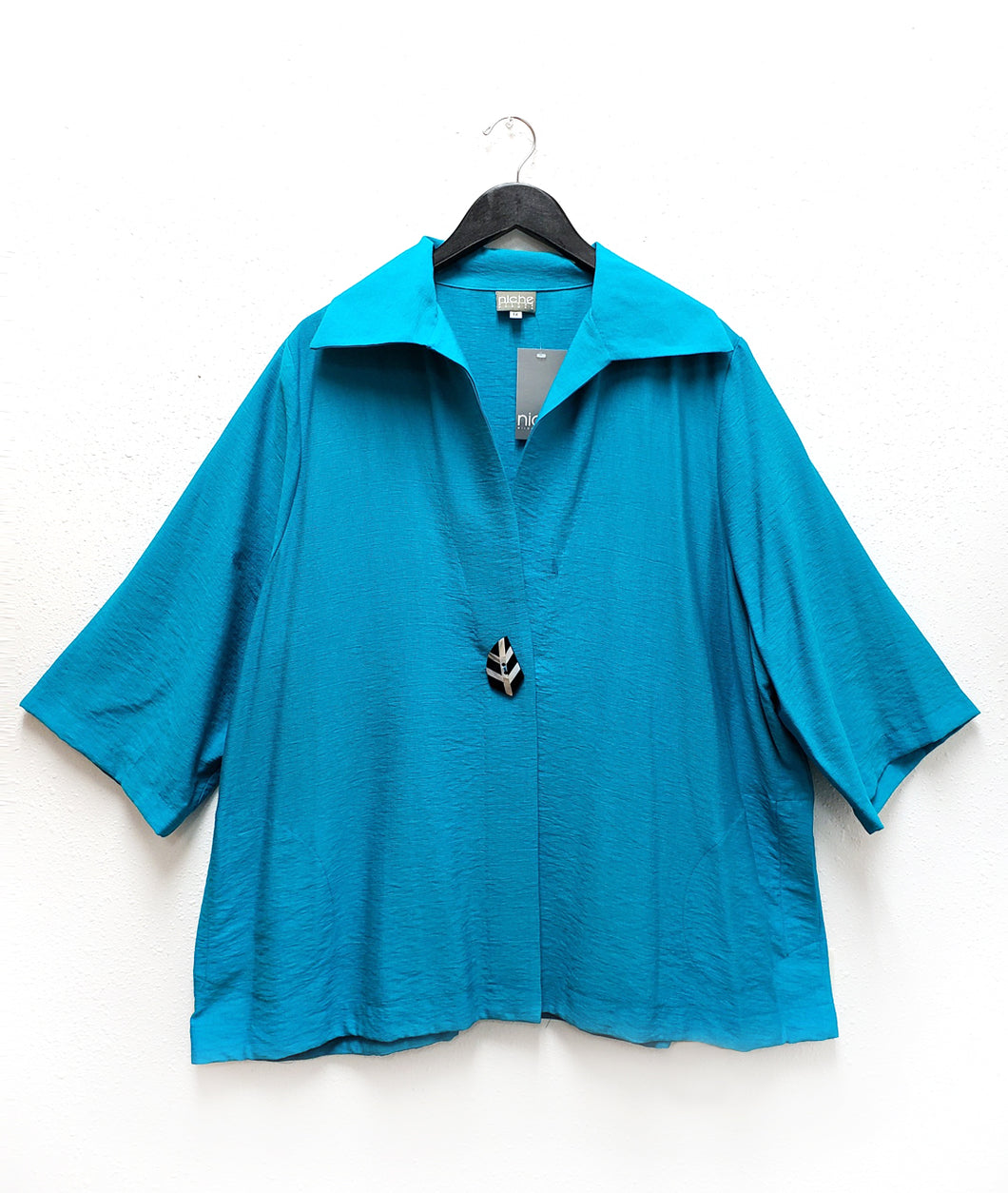 turquoise blue jacket with a single black and white leaf button and a large collar