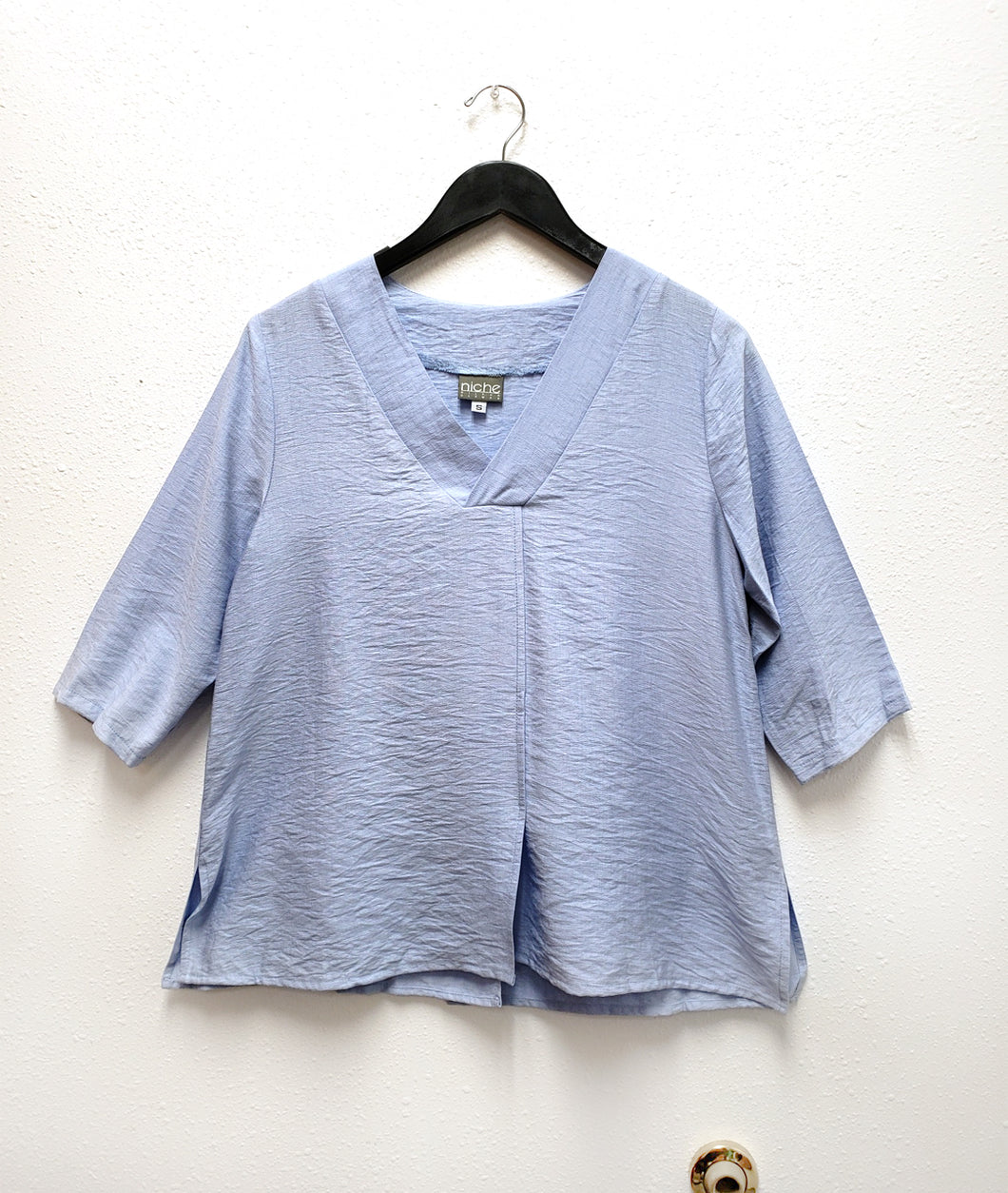 light blue top with a vneck and 3/4 sleeves. top has a center front seam and splits on either side.