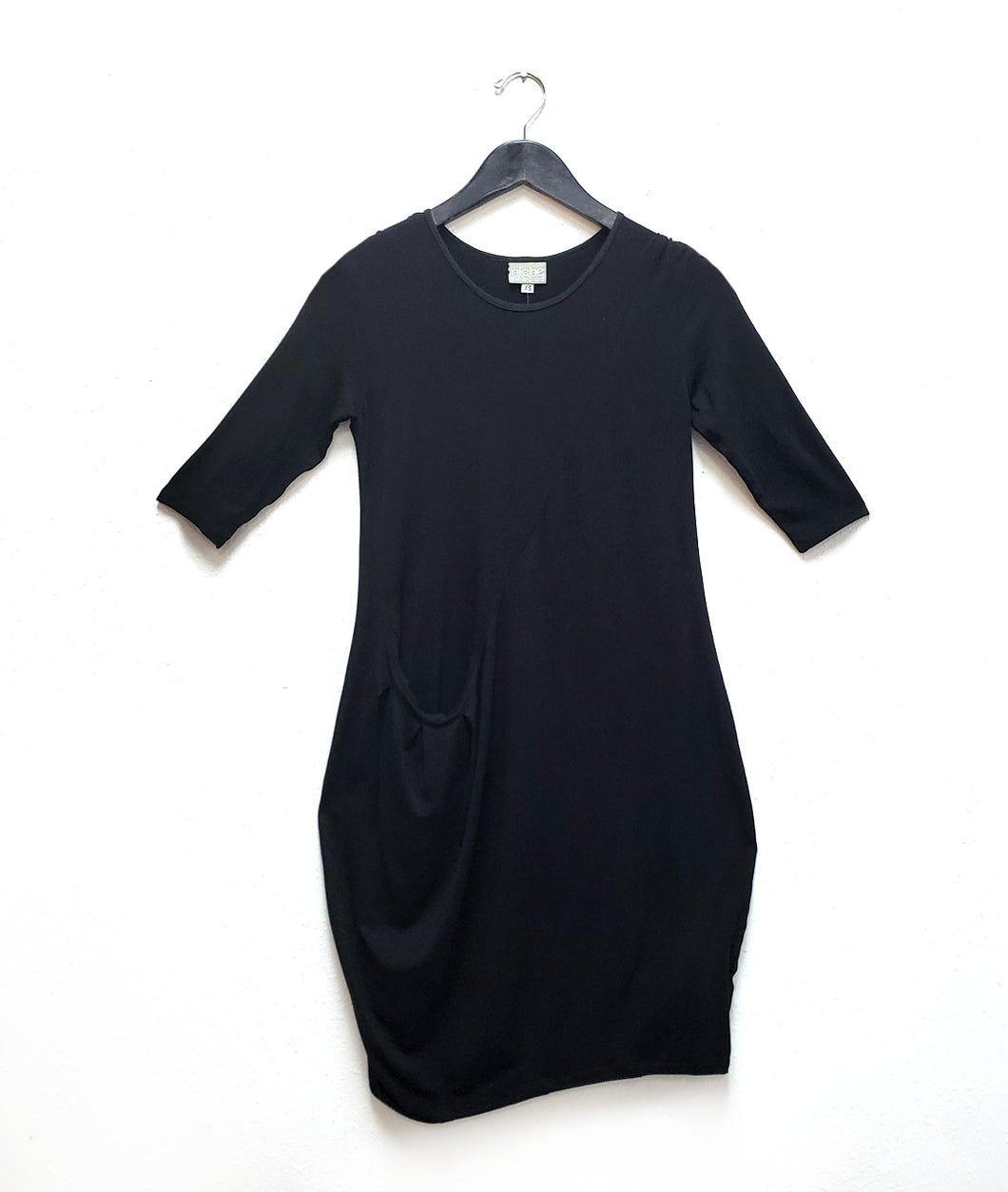 black dress with a diagonal seam across the body with a pocket set in the seam