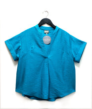 Load image into Gallery viewer, blue pullover boxy top with a vneck, small rolled sleeves and a curved bottom hem