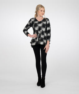 model in a black and silver checker print vneck top