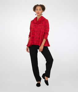 model in a red web print knit top worn with black pants