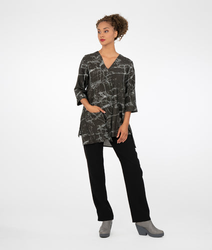 model in a slim black pant with a black marble print tunic with a vneckline, 3/4 sleeves an uneven hemline and a single square pocket on the hip