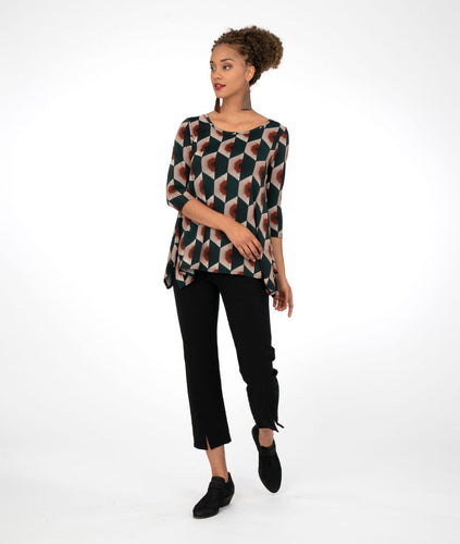 model in a green/red/white/black multi colored fan print top, with black pants, in front of a white background