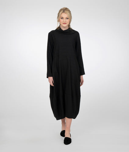 model in a long black dress with pockets set in the side seam and a cowl neckline