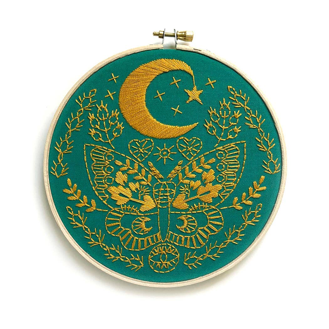 photo of embriodery hoop with dark teal fabric and yellow thread design of large moth, half moon and star, and florals and hearts around the main images. Against a white background.