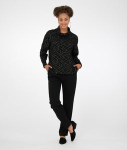 model in a slim black pant with a black boxy cowl neck top with a geometric grey pattern