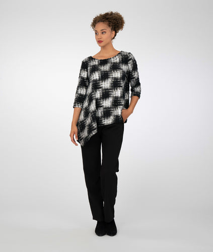 model in a black and silver checkered top with black pants. top has an angled hemline