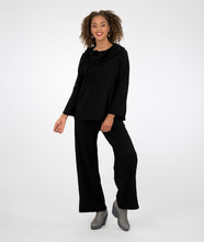 Load image into Gallery viewer, model in a textured black pant with matching top. top has a rounded collar with a drawstring