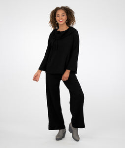 model in a textured black pant with matching top. top has a rounded collar with a drawstring