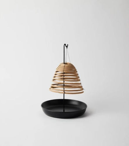 Pictured against a white background is a black, metal citronella holder. The base is round and solid with a rod attachment in the middle that holds hanging citronella or incense. Displayed hanging off of the rod is a circular citronella coil.