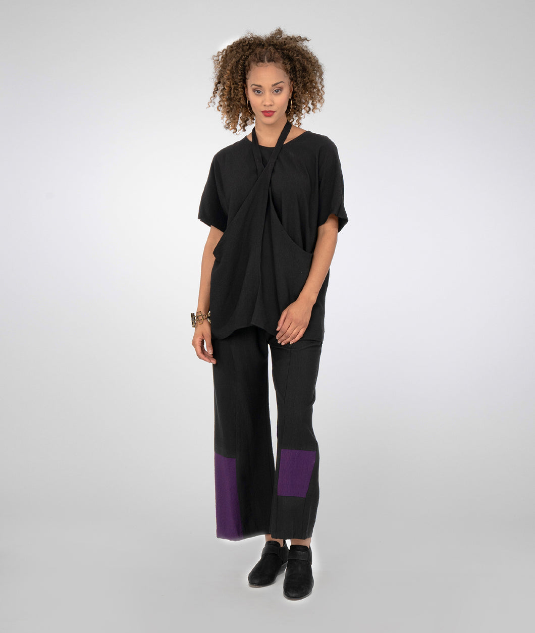 model in a black pant with deep purple color blocking, worn with a black top with extrended sides joined by a strap worn around the neck, halter style