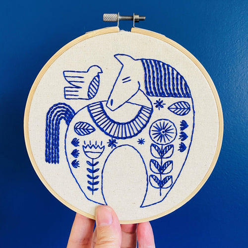 embroidery hoop with a blue horse and bird design held up buy a hand