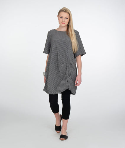 model in grey/white brick patterened tunic with black leggings in front of a white background