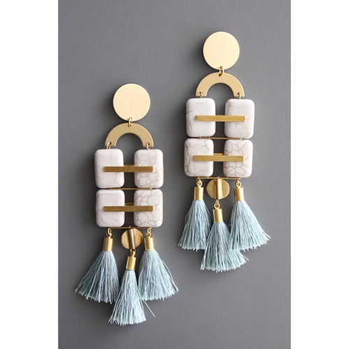 close up of deco earrrings with brass posts and discs, 4 rectangular white stone drops, and three aqua silk tassels