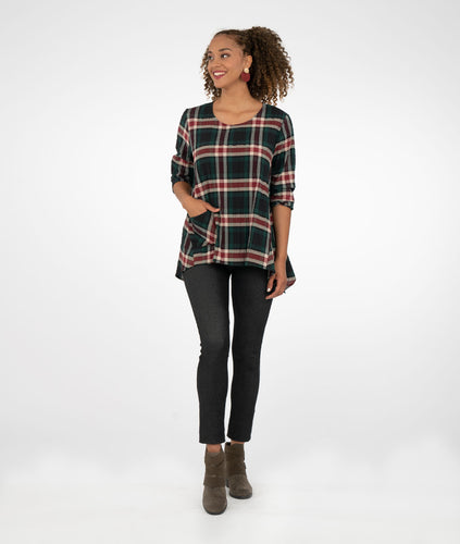 Model in a green/red/white plaid top and demin leggings in front of a whtie background