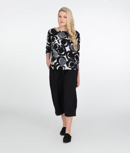 model in a black, white and grey circle print top with a dolman style sleeve