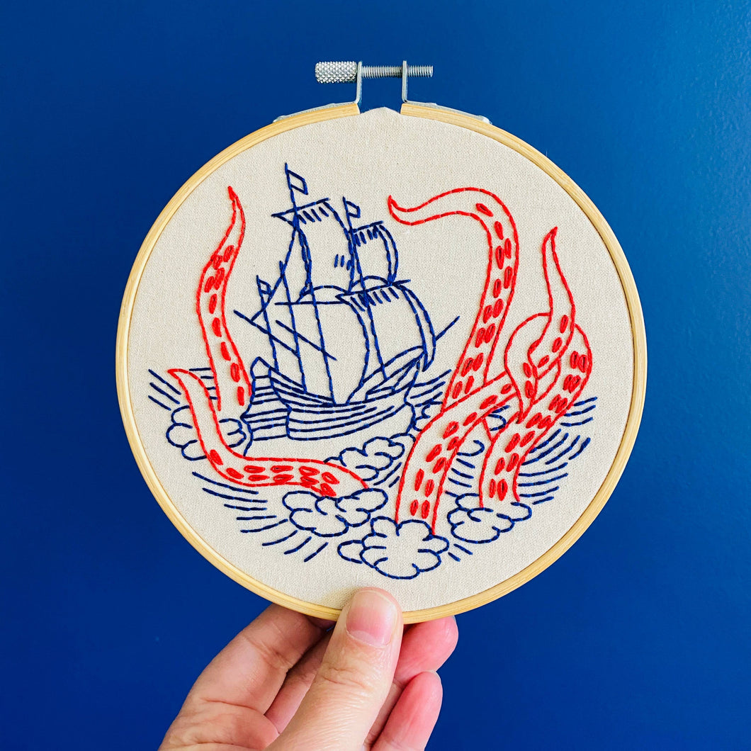 embroidery hoop with a ship on the water with large tentacles surrounding it design held up buy a hand
