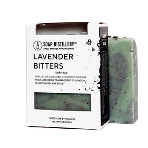 "Photo of mint green bar of soap with black speckles next to a packaged bar of soap in a black and white box with a label that says ""Lavender Bitters"" with a description."