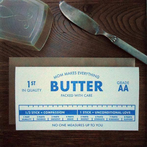 close up of greeting card made to look like a package of butter. Laying on a wood table with a butter knife and butter saver in the background.