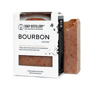 "Photo of a brown speckled  bar of soap next to a packaged bar of soap in a black and white box with a label that says ""Bourbon"" with a description."
