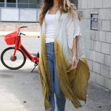 close up of model wearing a white t-shirt and jeans and an open loose kimono with fringe edge that is white on tops and fades to dark dijon color starting at waist. In the background is a red bicycle, cinder wall and street