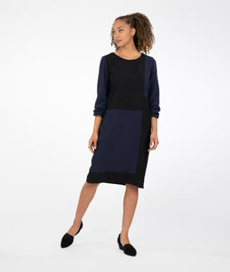 model in a black and navy color blocked dress with long sleeves and a round neckline