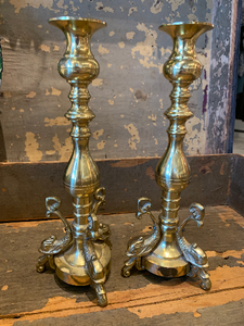 Pictured against a wooden background are two identical brass antique candlesticks. The candlesticks feature three ornate koi fish at the base of each candlestick.
