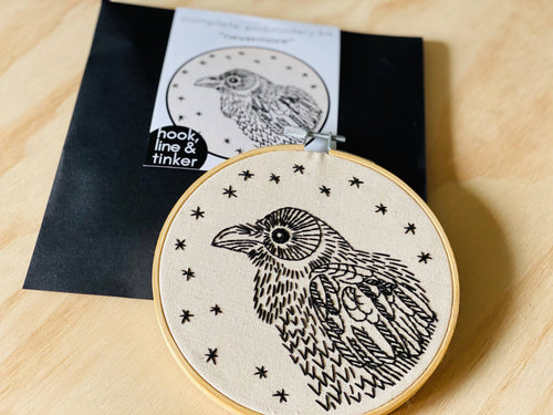 envelope and embroidery hoop with a black raven design