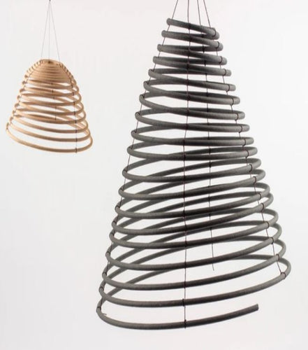 Pictured against a white background are two citronella coils that are hanging. The smaller coil is on the left and is light brown; the coil on the right is the larger coil and is black in color.