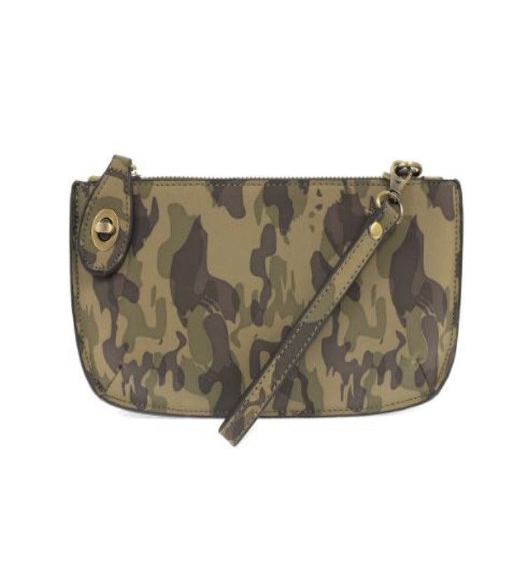 Pictured against a white background is a small clutch that features an olive themed camouflage print. The clutch features gold hardware, a wristlet attachment, and a small gold clasp on the top left corner of the clutch.