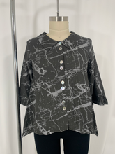 Load image into Gallery viewer, Body form wearing a 3/4 sleeve button up top with collar. The top features a black marbled print.