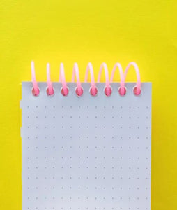 Pictured against a yellow background is a notepad that has a pink coil binding at the top. The paper features a grid dot line format.