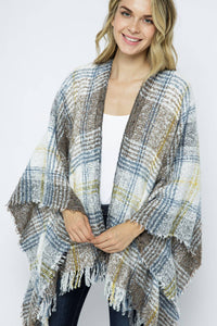 model wearing soft plaid poncho in grey, yellow, and blue with fringe