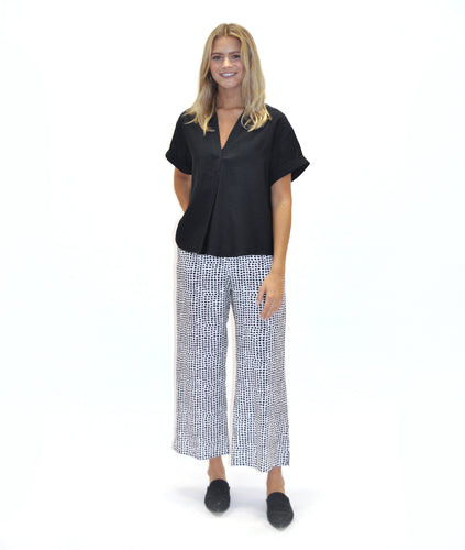model in a black a white dot print pant with a solid black top with a vneck and pleat down the center front