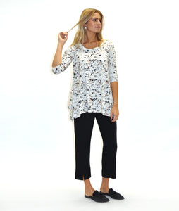 model in a white terrazzo print top with a hankerchief hem, worn with a slim black pant with a split at either ankle front