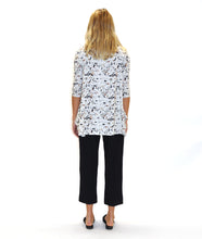 Load image into Gallery viewer, model in a white terrazzo print top with a hankerchief hem, worn with a slim black pant with a split at either ankle front