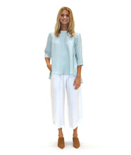 Load image into Gallery viewer, model in a light green pull over top with a flowy high-lo hem, with white pants and tan shoes