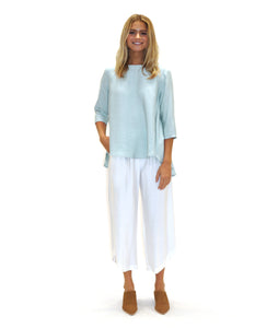 model in a light green pull over top with a flowy high-lo hem, with white pants and tan shoes