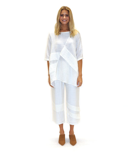 model in a white pullover top with asymmetrical fold detailing along the front, with a 3/4 sleeve and matching pants