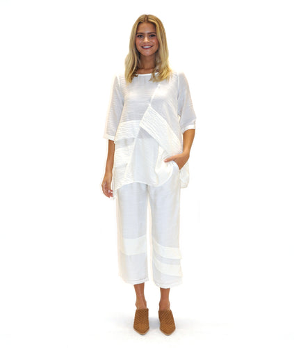 model in a white top and bottom with decorative pleating across the body and pant legs