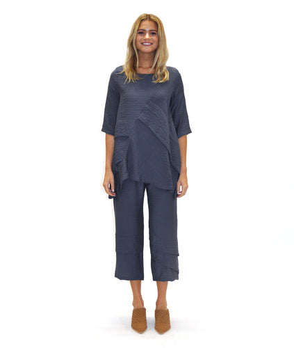 model in a blue/grey pullover top with asymmetrical fold detailing along the front, with a 3/4 sleeve and matching pants