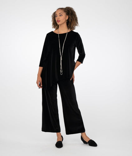 model in a black asymmetrical top with a wide leg pant, in front of a white background