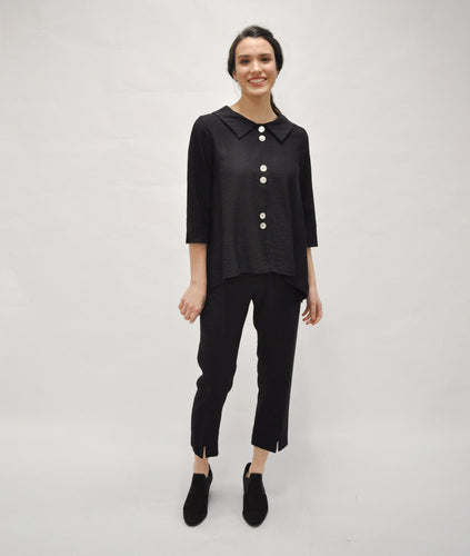 model in a black buttoned blouse with a slim black pant with a split at the ankle of each center front leg seam