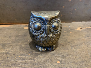 Pictured against a wooden background is an antique small brass owl.