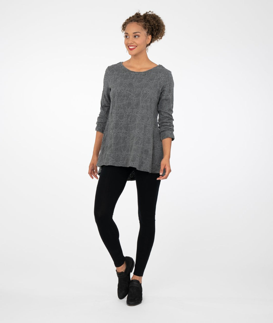 model in black leggings with a long pull over simple gray sweater top, in front of a white background